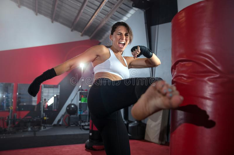 Close up action lifestyle portrait of an active sweaty athletic female mma fighter kicking a bag, gym training, self defense and e. Strong female athlete fighter royalty free stock photos