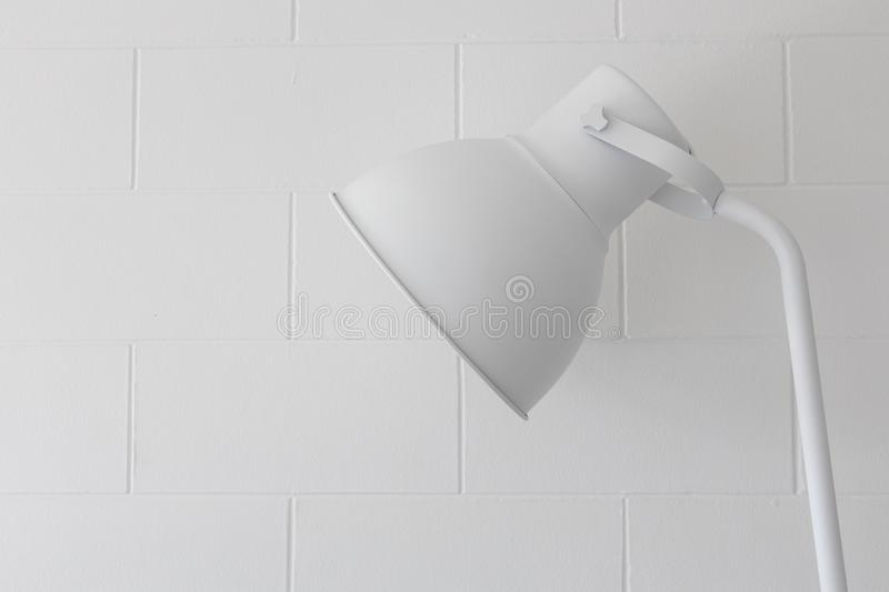 Close up of adjustable single simple modern white lamp on block brick wall texture background royalty free stock image