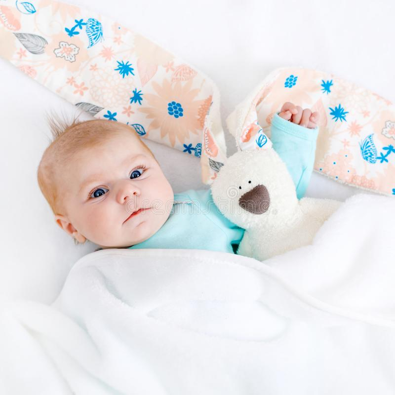 Close-up of adorable cute newborn baby girl of two months on white background. Lovely child playing with plush rabbit. Toy wigh bit long ears. Holiday, Easter royalty free stock images