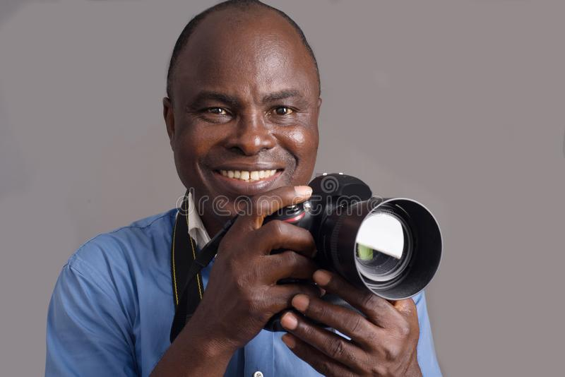Close-up of an adult african man and camera, smiling stock photo