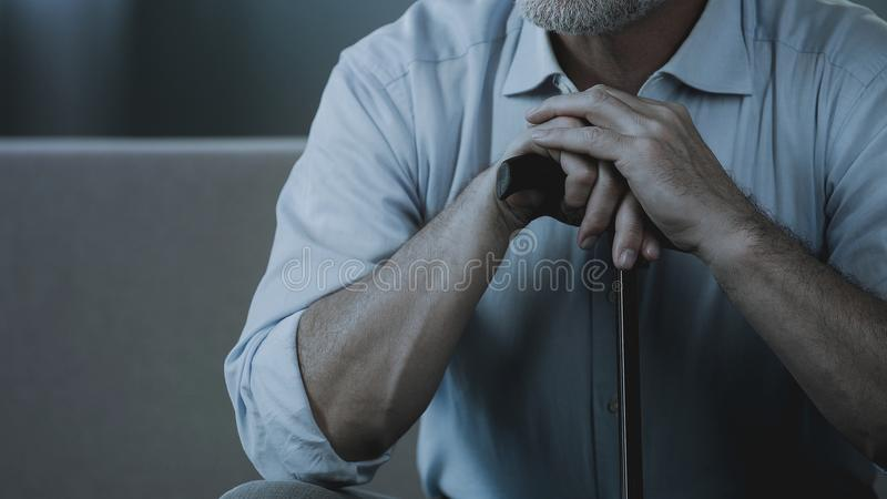 Close-up of adult male hands holding walking stick, old man sitting on sofa royalty free stock photography