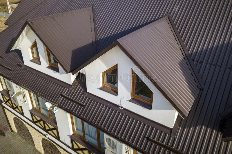 Close-up aerial view of building attic rooms exterior on metal shingle roof, stucco walls and plastic windows stock photo