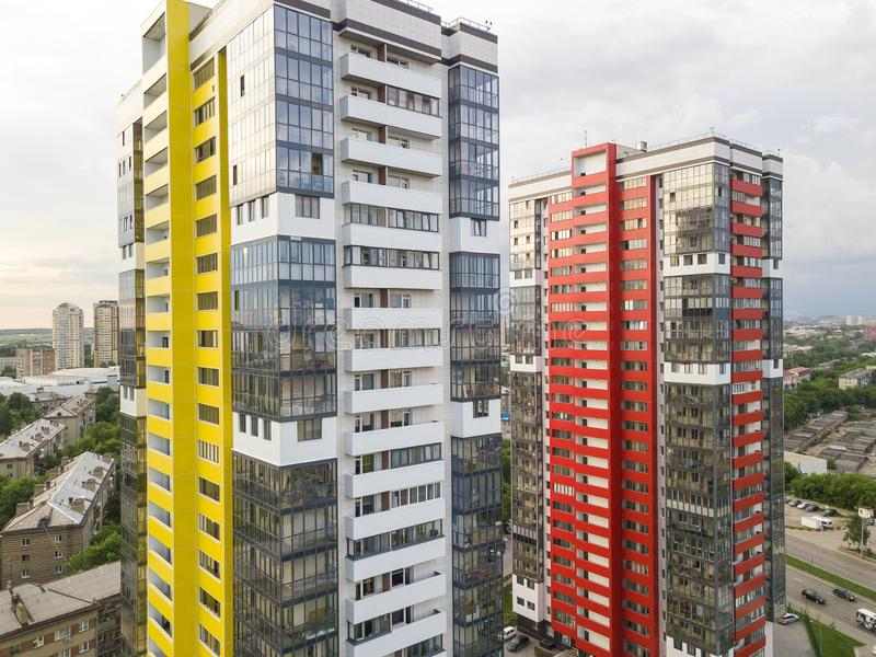 Close-up aerial view of two tall skyscrapers of red and yellow colors. Among small buildings with parking for cars and a children`s playground in the yard with royalty free stock photo