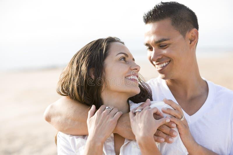 Close up of affectionate Hispanic couple on beach royalty free stock photos