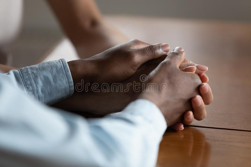 Close up of biracial couple hold hands showing love. Close up of african American couple hold hands on wooden table make peace reconcile after fight, biracial royalty free stock image