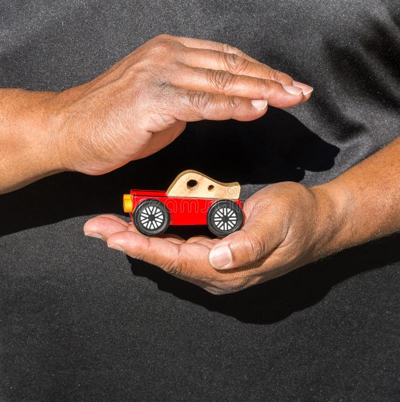Close up of African American man`s hands cupped around a toy car. Close up of African American man`s hands cupped around a red wooden toy car against his black stock photos