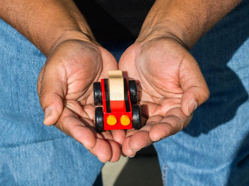 Close up of African American man`s hands cupped around a toy car viewed from above. Close up of African American man`s hands cupped around a red wooden toy car royalty free stock image