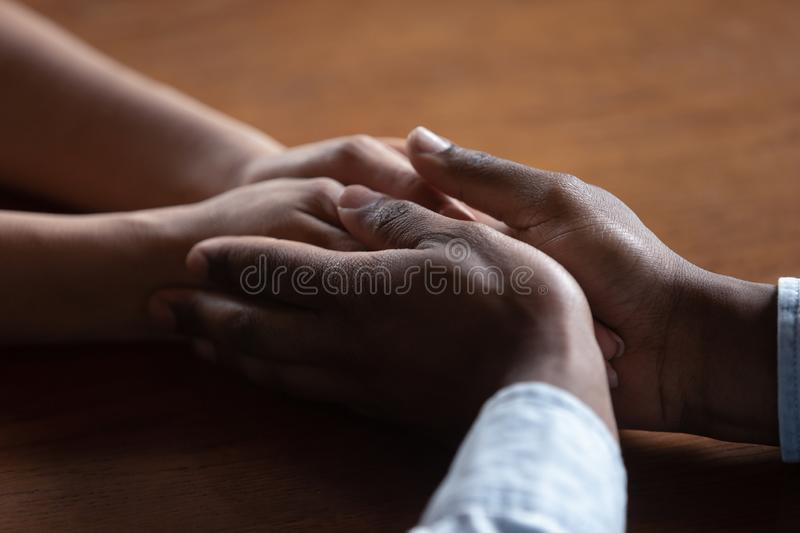 Close up of biracial couple hold hands having romantic moment stock images