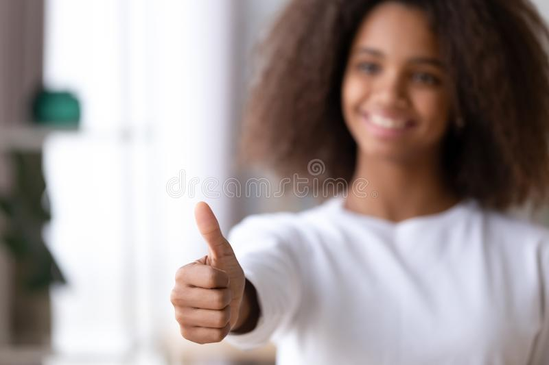 Close up African American teenage girl showing thumbs up, like. Smiling African American teenage girl showing thumbs up, like, satisfied black teenager royalty free stock photo