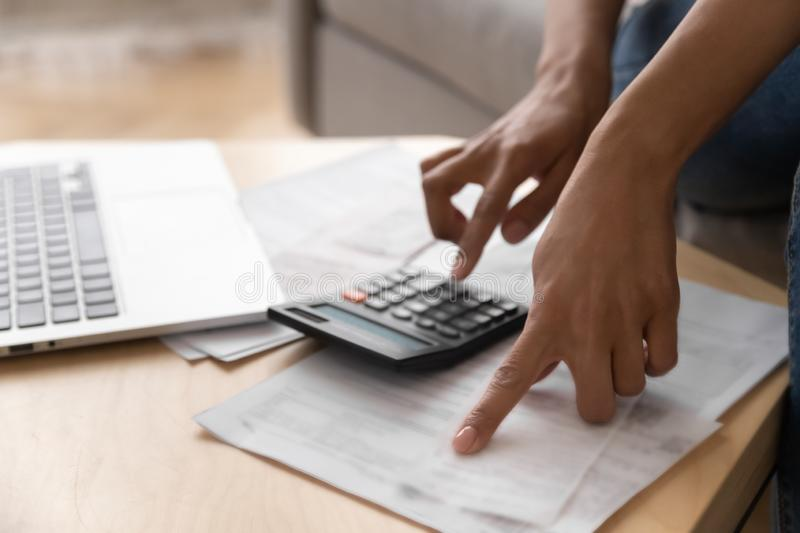 Close up African American woman using calculator, calculating finance stock photography