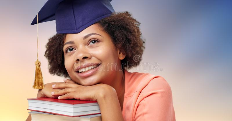 Close up of african graduate student with books. Education, school, knowledge and graduation concept - close up of happy smiling african american graduate stock photography