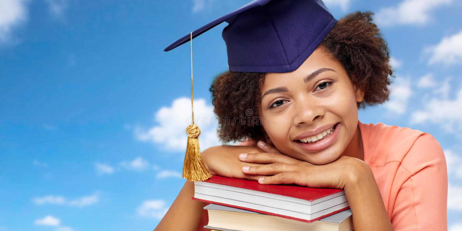Close up of african graduate student with books. Education, school, knowledge and graduation concept - close up of happy smiling african american graduate stock photos