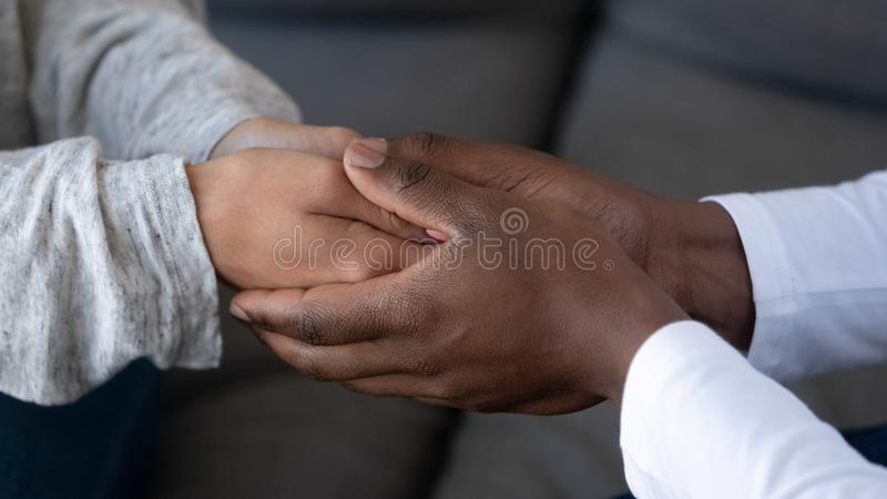 Close up of african husband holding hand of white wife stock photography