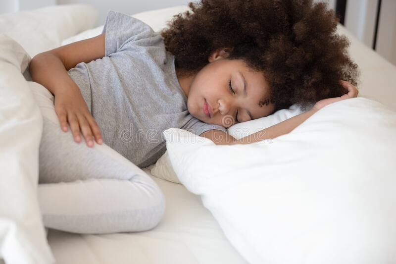Close up african little girl sleeping in bed at home. Close up african 6 years old adorable girl closed eyes lying in bed sleeping on white bed clothes stock images