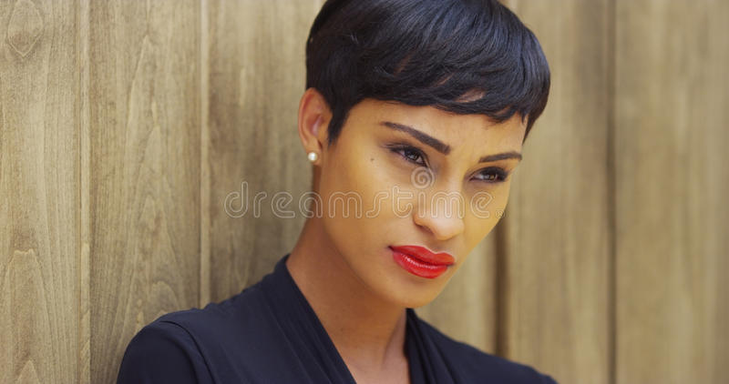 Close up of African woman in black dress and red lipstick leaning against wall royalty free stock image