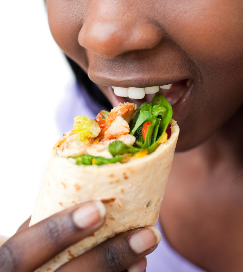Close up of an african woman devouring a burrito. Against a white background stock photos