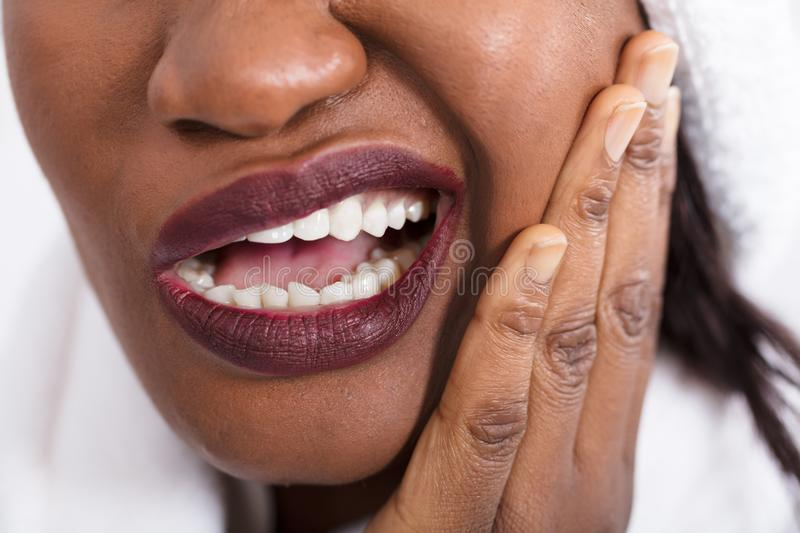 Woman Suffering From Tooth Ache. Close-up Of An African Woman Suffering From Tooth Ache royalty free stock photography