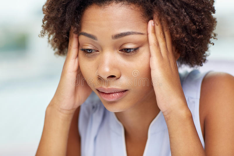 Close up of african young woman touching her head. People, emotions, stress and health care concept - unhappy african american young woman touching her head and royalty free stock photos