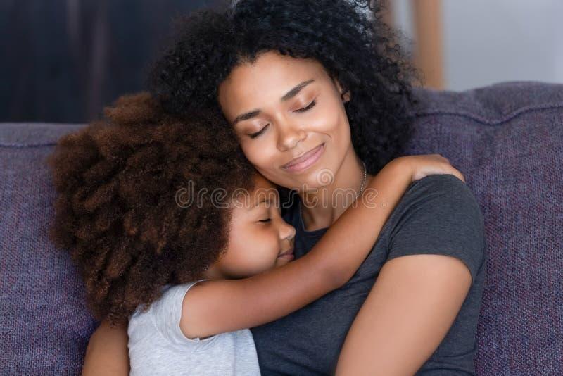 Close-up Afrikaanse dochter die moederzitting op laag thuis omhelzen stock afbeelding