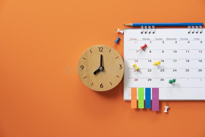 Close up of alarm clock and calendar on the orange table background royalty free stock images