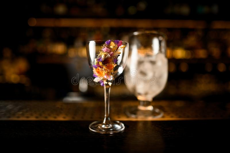 Close-up of alcohol cocktail and glass with ice on a counter. Close-up of an alcohol cocktail with flower and glass with ice on a wooden and metal bar counter royalty free stock image