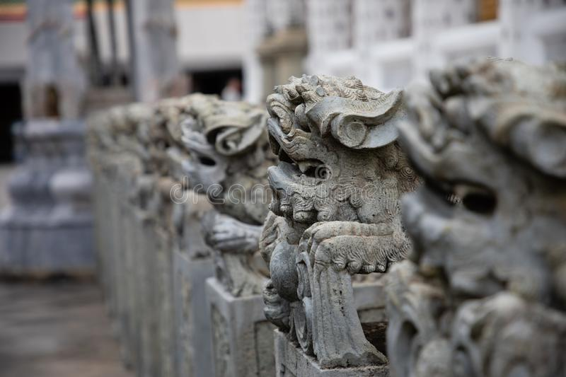 Close up of aligned stone animal statues from a temple at Bangkok stock photography