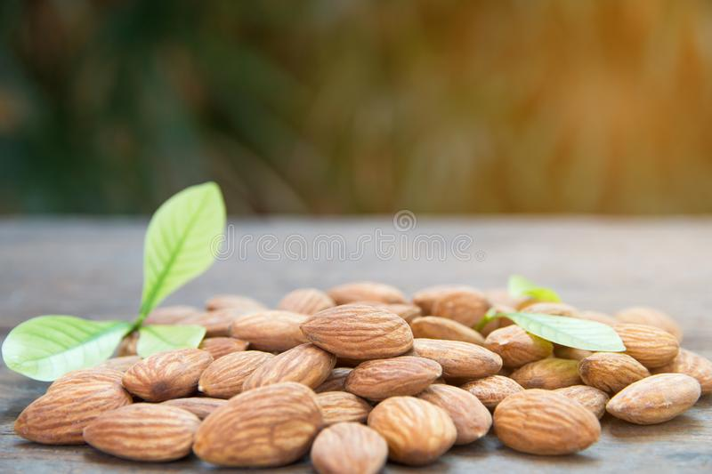 close up of almonds grain roast on wood background with green le stock photo