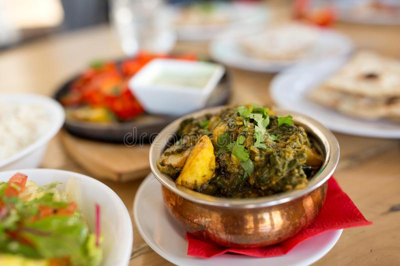 Close up of aloo palak dish in bowl on table. Food, south asian cuisine, culinary and cooking concept - close up of aloo palak dish in bowl on table of indian stock image