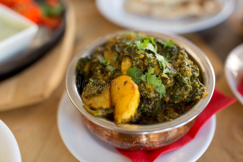 Close up of aloo palak dish in bowl on table. Food, south asian cuisine, culinary and cooking concept - close up of aloo palak dish in bowl on table of indian royalty free stock photos