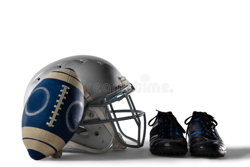 Close up of America football and helmet by sports shoes. On white background stock photos