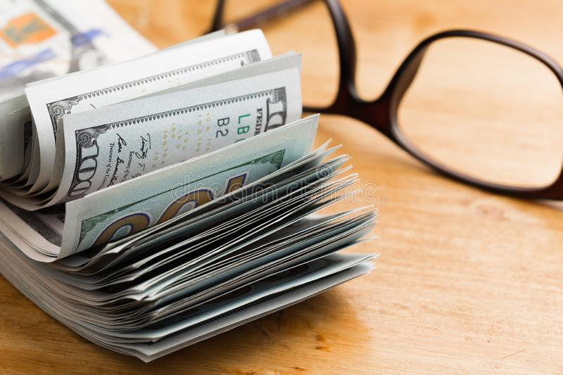 Close-up american dollar banknotes on wooden table with glases stock photo