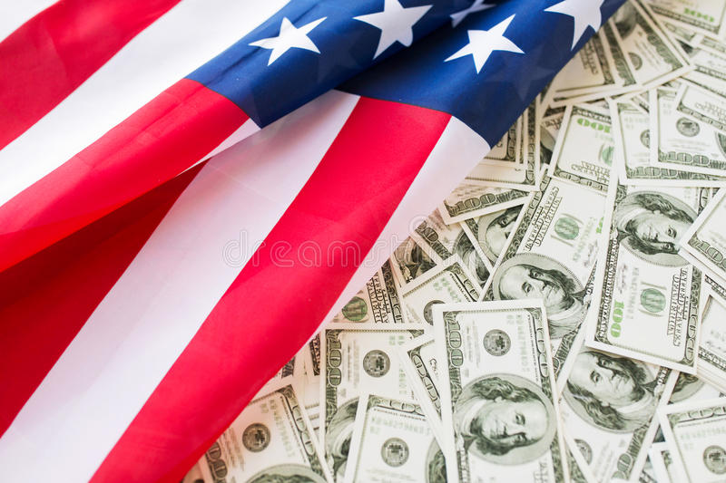 Close up of american flag and dollar cash money. Budget, finance and nationalism concept - close up of american flag and dollar cash money stock image