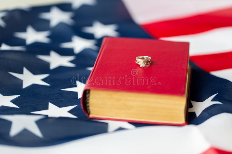 Close up of american flag, wedding rings and bible stock photography
