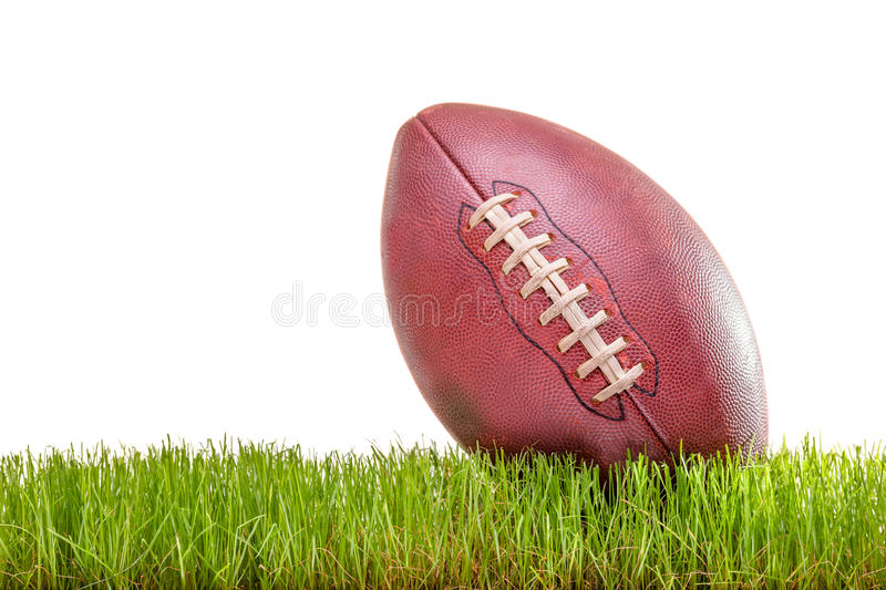 Close-up on an American football. On a grass surface isolated on white background royalty free stock photography