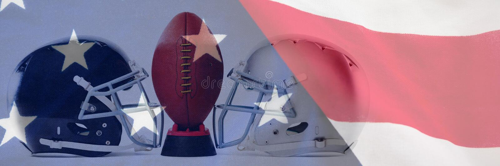 Composite image of close up of american football on tee by sports helmets. Close up of American football on tee by sports helmets against close-up of an american stock photography