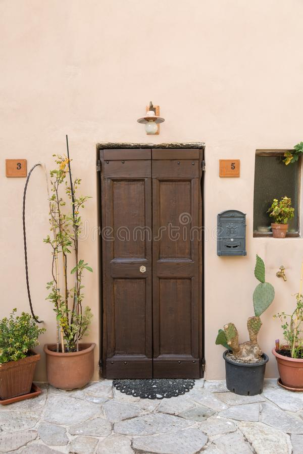 Close-up of Ancient Brown Wooden Door and Decorative Plants royalty free stock images