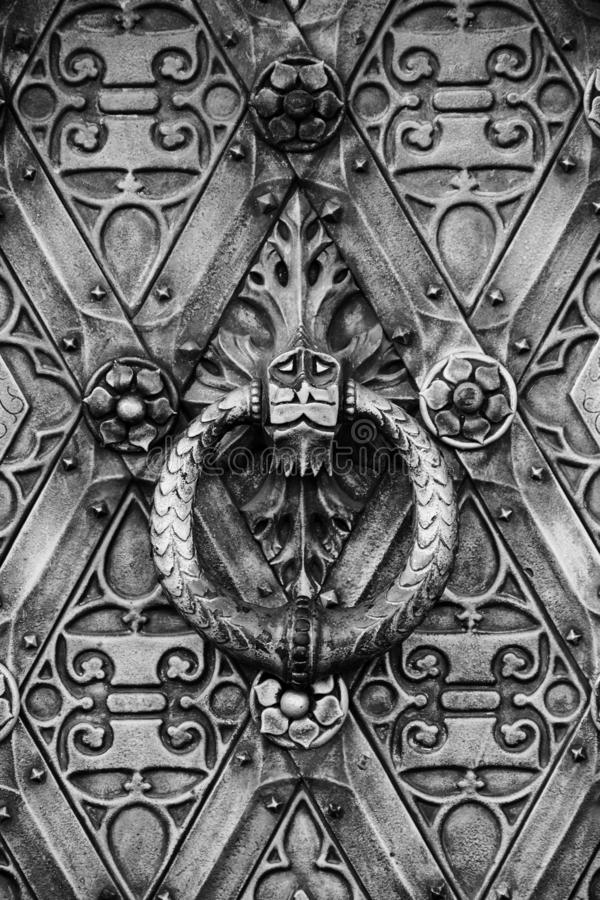 Old ancient iron detailed decorated door with a door knocker stock image