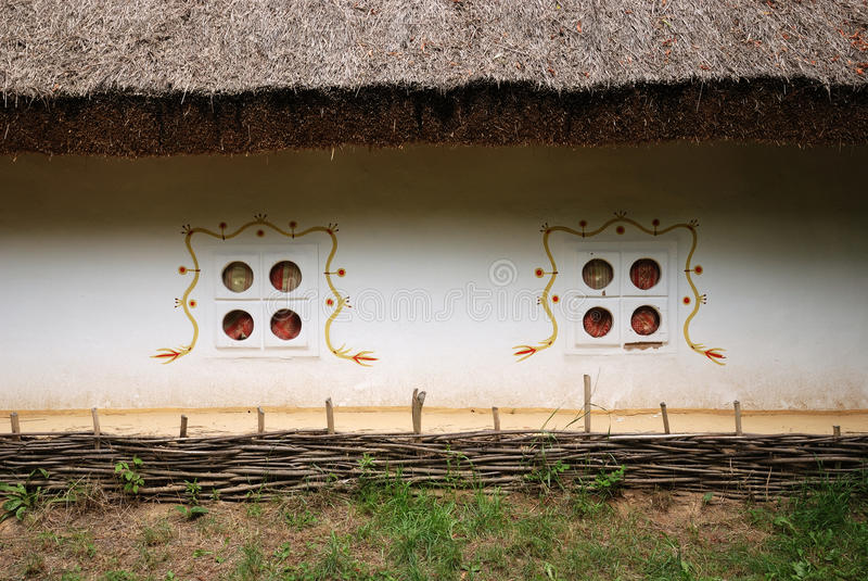 Close-up of ancient Ukrainian hut. Vintage house is made in Ukrainian folk style of 17th century. The white wall with ornamented windows is covered with a thatch stock photo