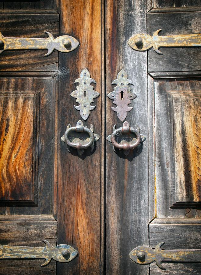 Close up of ancient varnished wooden double doors with ornate brass and metal decoration keyholes and handles stock photo