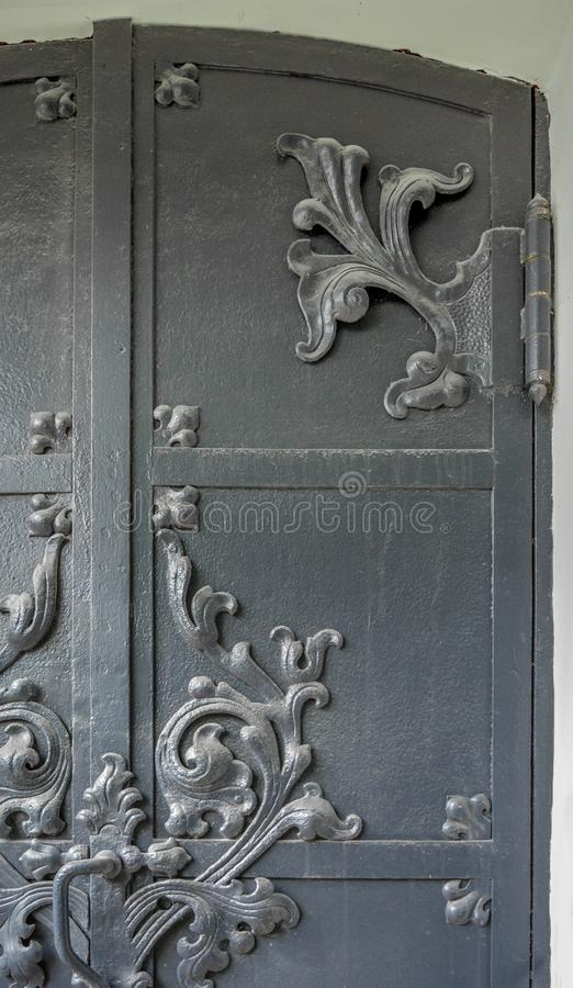 Close-up of ancient vintage metal door with cast iron floral deorative ornament royalty free stock photography