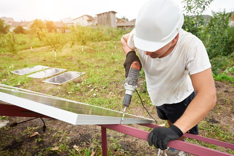 Installation of stand-alone exterior photo voltaic panels system. Renewable green energy generation. Close-up angled view of technician working with screwdriver royalty free stock photos