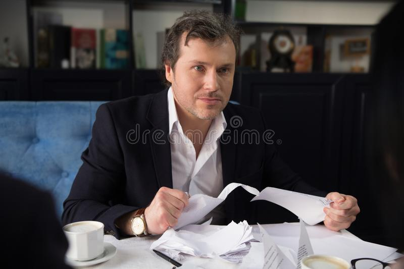 Business people discussing agreement condition. Close up of angry businessman looking at partners and torning agreement stock photo