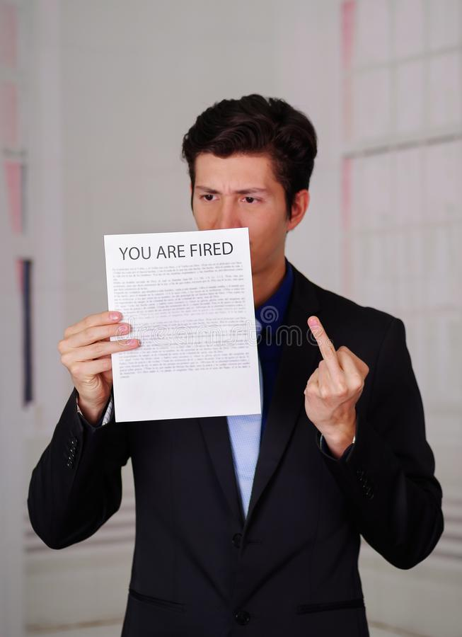 Close up of angry businessman wearing a suit and holding a sheet of paper of you`re fired text on it, doing a middle. Finger sign, in a blurred background royalty free stock photography