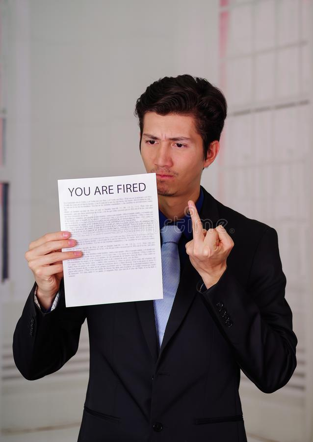 Close up of angry businessman wearing a suit and holding a sheet of paper of you`re fired text on it, doing a middle. Finger sign, in a blurred background royalty free stock image