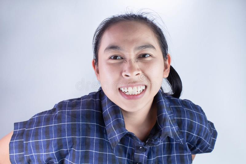 Close-up Angry face of Asian young woman in blue shirt with look to the camera stock photos