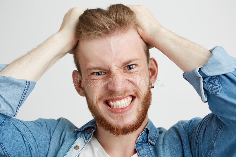 Close up of angry rage young man touching his hair looking at camera clenched teeth over wite background. Copy space stock image