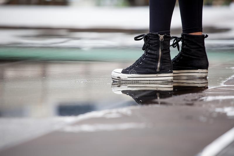 Close up Ankle Sneakers of woman standing on water puddle on street in city stock photos