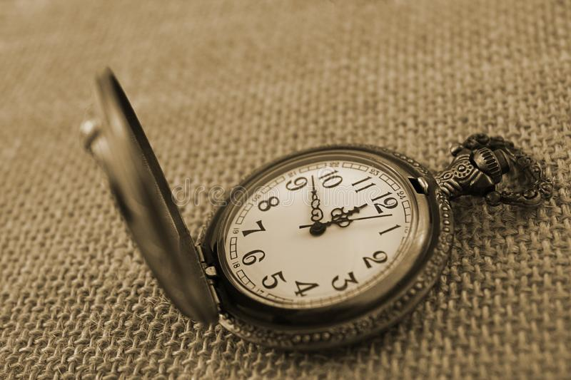 Close-up antique brass metal pocket watch displayed on burlap background. This close-up photograph features an antique brass copper metal pocket watch displayed royalty free stock photo