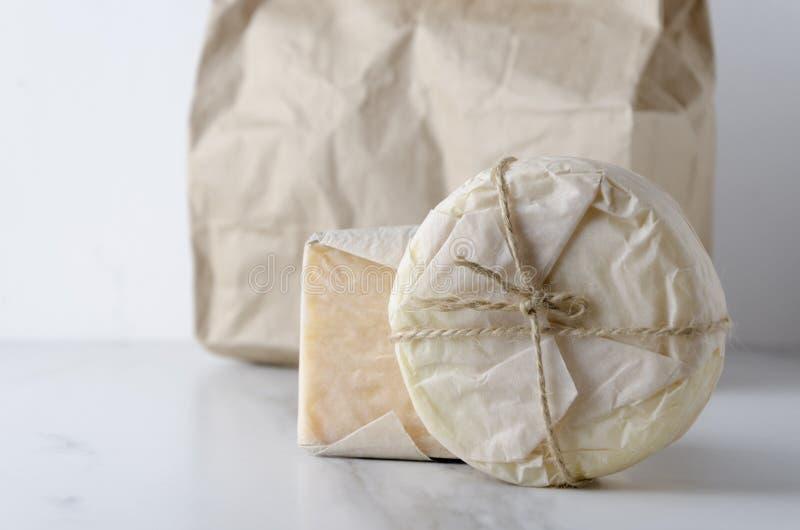 Close up apenas de partes compradas de queijo contra o saco de papel na tabela branca fotografia de stock royalty free