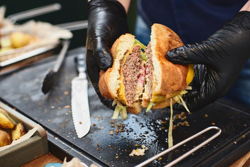 Close up of appetising beef burger. Chef`s hands divide into half cooked hamburgers from beef. Street food ready to. Serve on a food stall. Chef cooks an royalty free stock photography